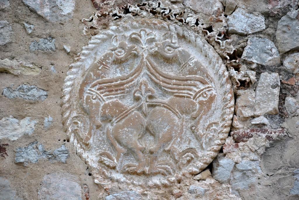 Grifoni u medaljonu na priprati, oko njih ukrasni keramički cvetići