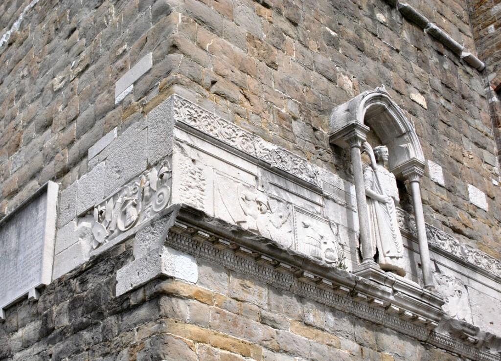 Skulptura svetog Đusta na zvoniku, okružena vojničkim frizom preostalog od rimskih građevina