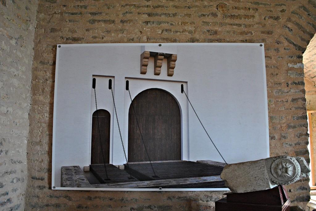 Ilustracija ulaznih vrata sa mostovima koji se podužu radi zaštite od upada neprijatelja. Na desnoj strani vidi se sačuvani deo ukrasa nad kolskim vratima