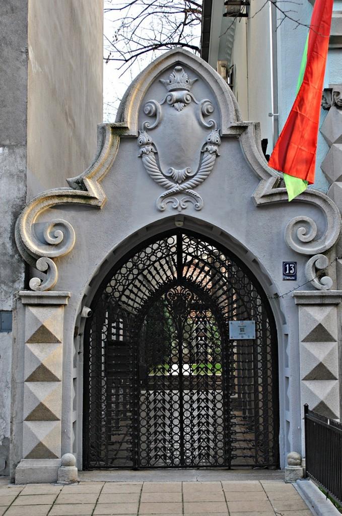 Kapija sa bogatom čipkom od kovanog gvožđa i ponovljenim motivima prelomljenog luka i baroknih voluta