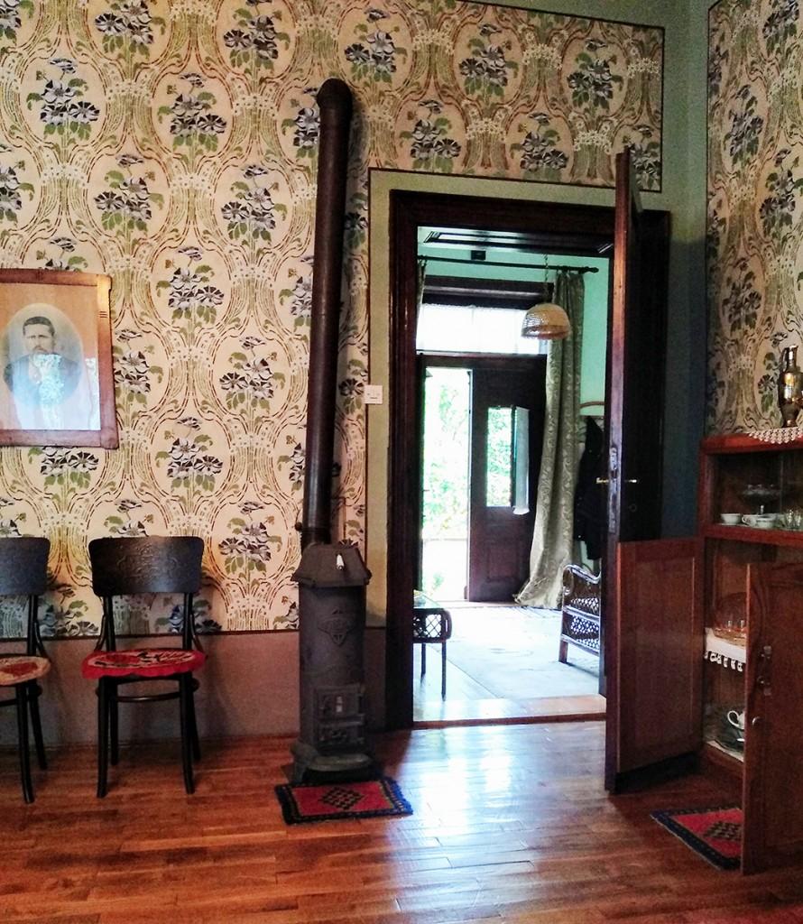 Pogled iz salona na ulazna vrata. Zidovi su oslikani karakterističnim biljnim motivima u stilu secesije, thenikom al seco